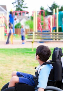 Disabled little boy in wheelchair sadly watching children play on playground